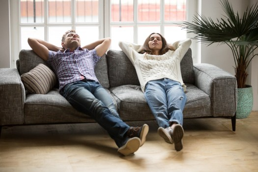 image of a man and a woman leaning back on a couch with their feet out taking a break