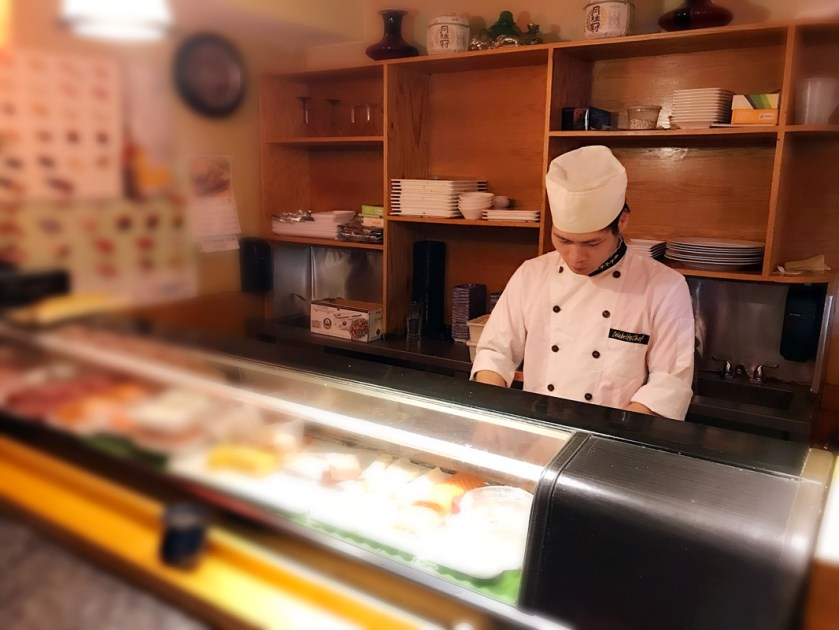 Person making sushi in cafe