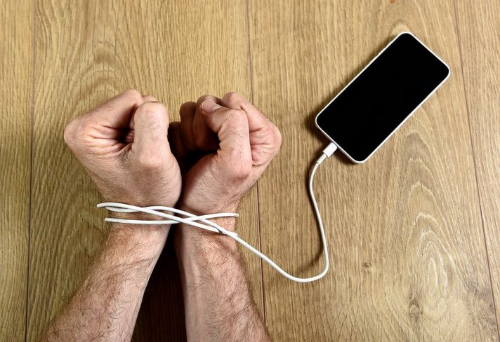 cell phone addiction and high screen time. man tied by charging cable of iphone