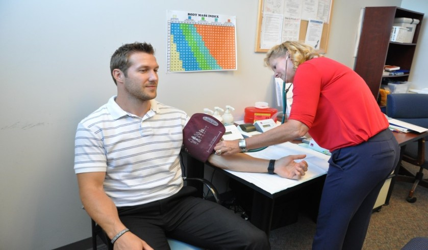 A student visiting the clinic to check his blood pressure