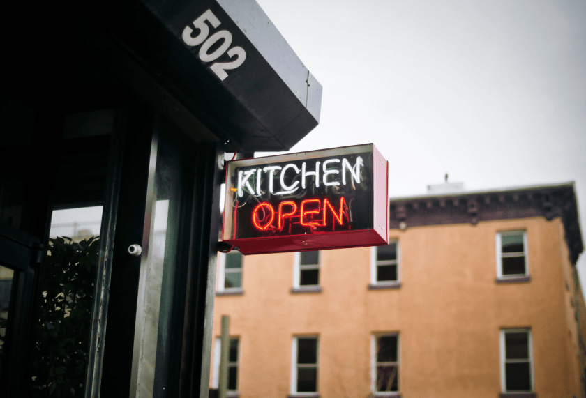 Picture of a neon light sign that says Kitchen Open