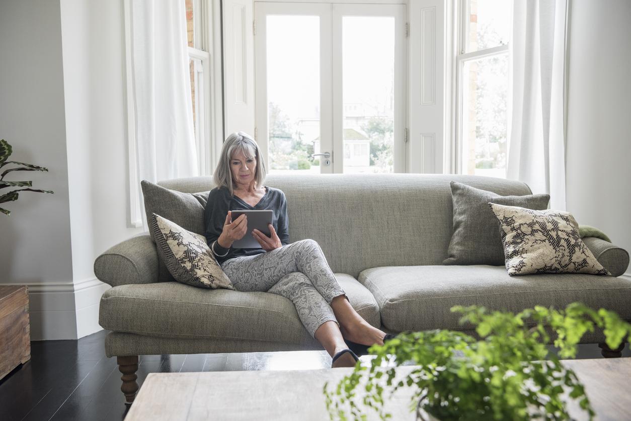 Senior woman sitting relaxing on the sofa using digital tablet