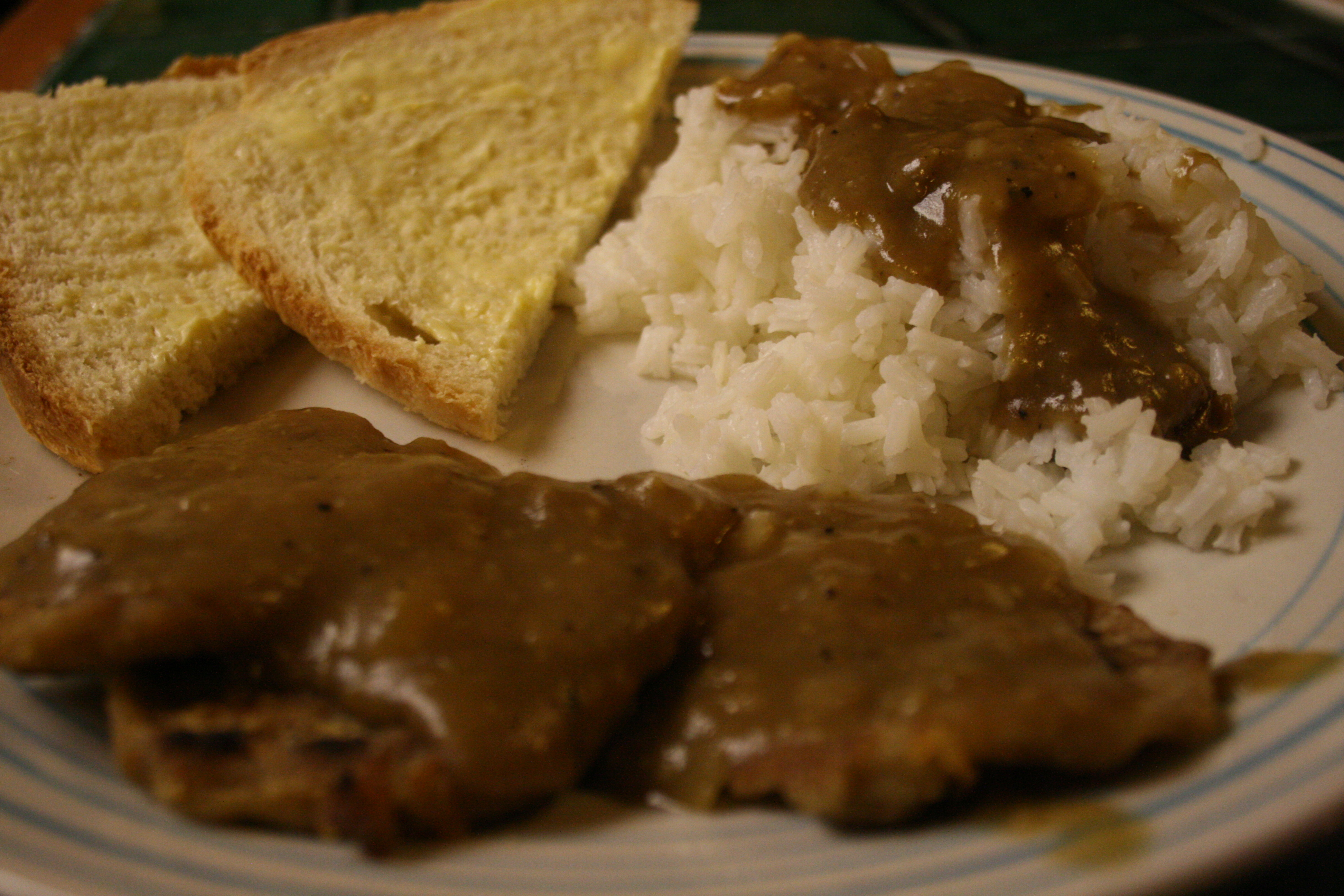 A delicious dinner of white flour and white rice covered in homemade gravy.