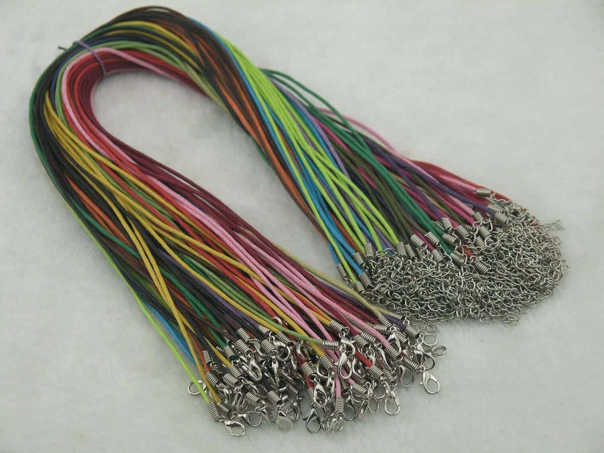 a bundle of cotton wax necklaces in bright colors from pink to blue, green, orange, and brown