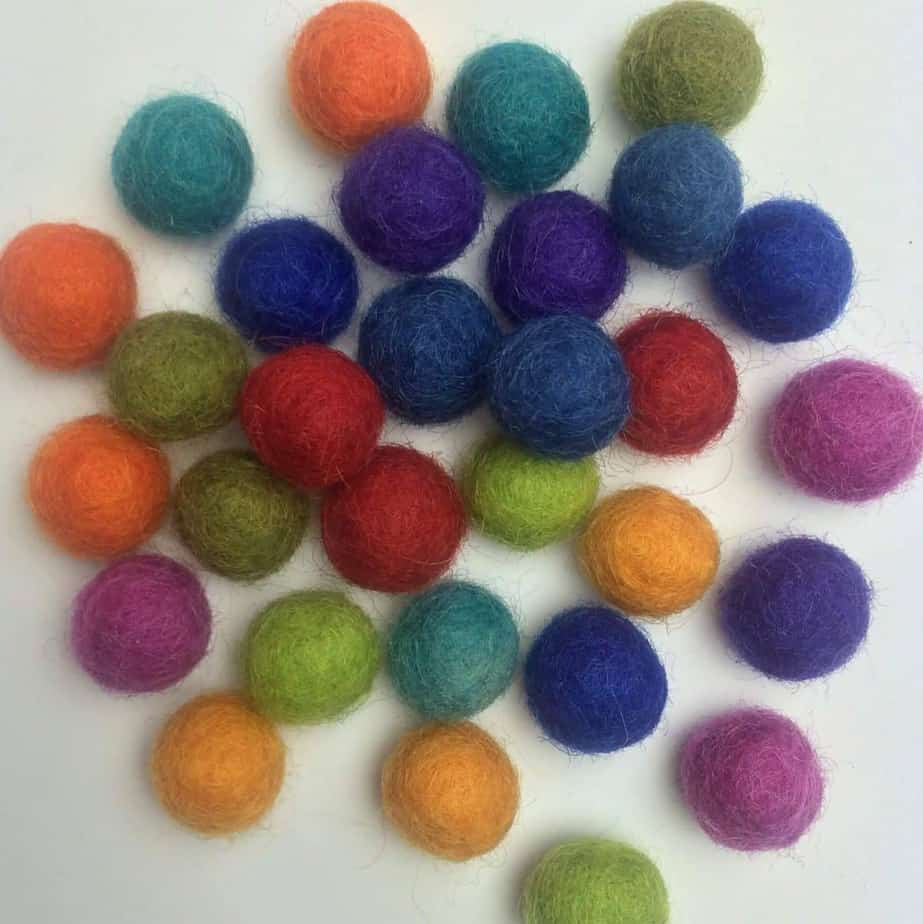 a pile of small colorful wool balls that will be used inside of the wire cage necklace pendants