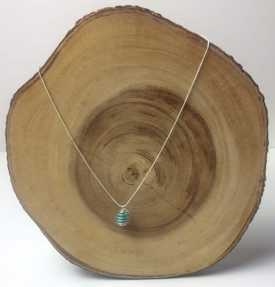 essential oil diffuser necklace displayed on slice of cedar tree to show what it would look like on neck