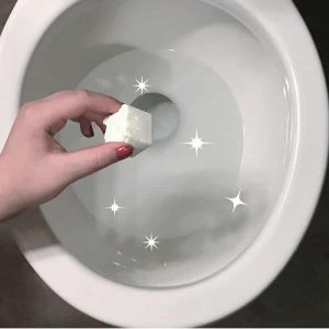 hand placing essential oil cleaning pod in toilet