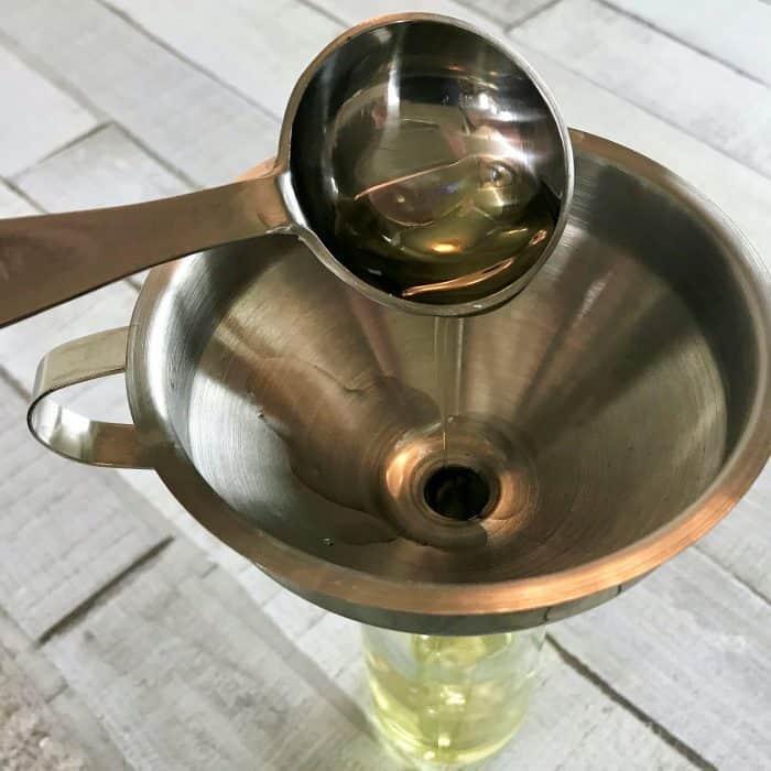 adding avocado oil to funnel and glass spray bottle for homemade hair serum