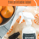 diy kitchen grease remover by two essential oil bottles and bowl of oranges
