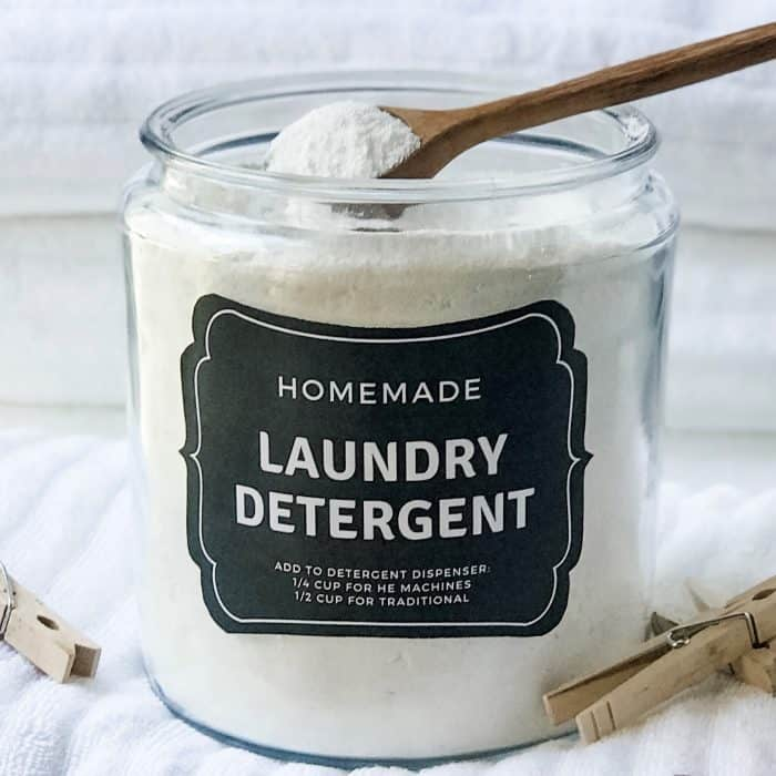 wooden spoon scooping out powder laundry soap from large glass cansiter, clothes pins and fluffy white towels surround the laundry detergent canister
