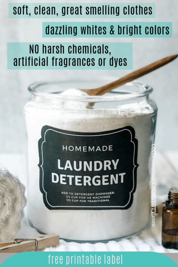 DIY natural laundry soap in large glass canister with free printable label, essential oil bottle, clothes pins, and fluffy white towels surround the canister