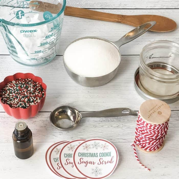 Sugar Scrub ingredients and tools display of coconut oil in measuring cup, organic non-gmo sugar in measuring spoon, red and green nonpareil sprinkles in cup, vanilla oleoresin in dropper bottle, wooden spoon, and custom lid labels