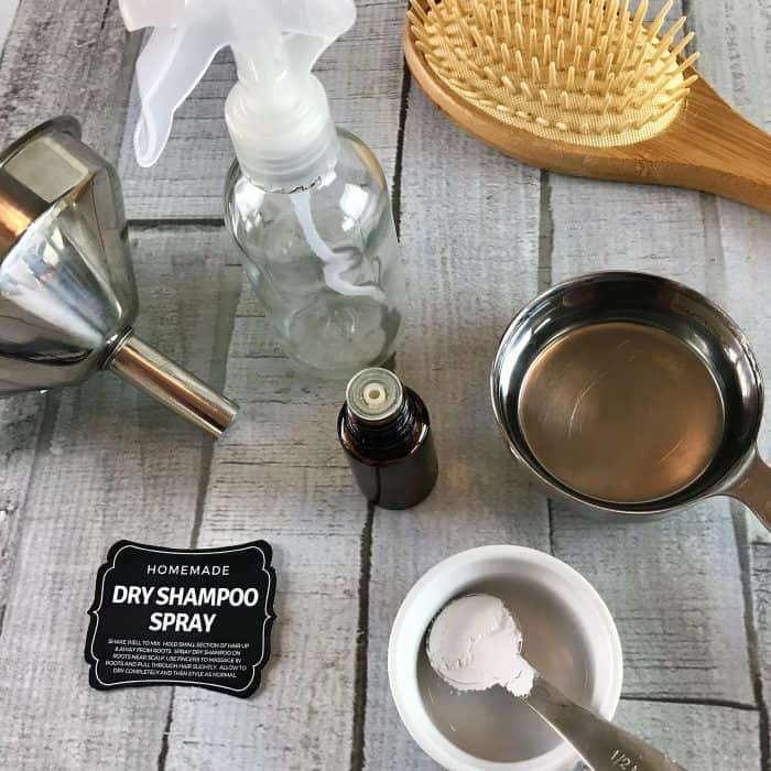 supplies to make homemade dry shampoo spray- funnel, spray bottle, vodka, calcium carbonate, essential oil