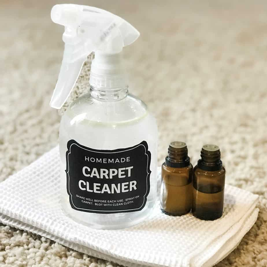 DIY carpet cleaner spray and two essential oil bottles on white cloth and carpet
