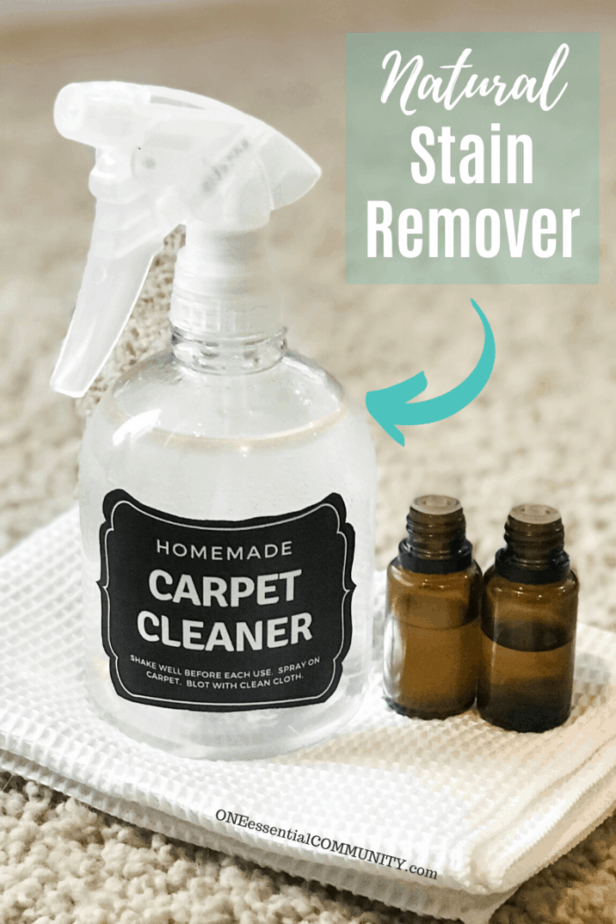 homemade carpet cleaner spray bottle, lemon essential oil, and tea tree essential oil on white cloth with words natural stain remover