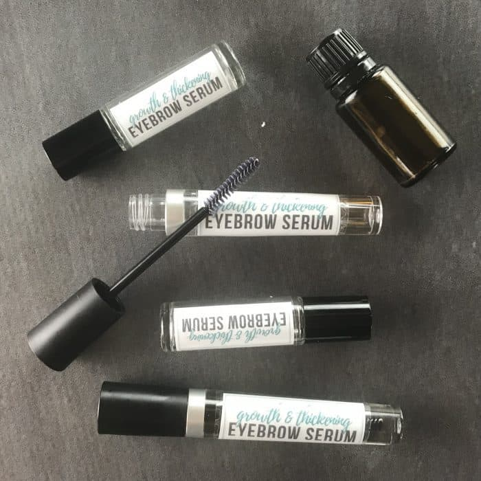 several bottles of homemade eyebrow growth serum, essential oil bottle, and applicator wand