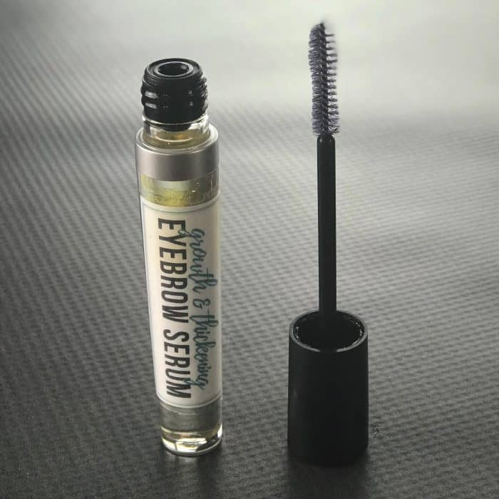 DIY eyebrow serum in mascara tube with applicator wand beside it