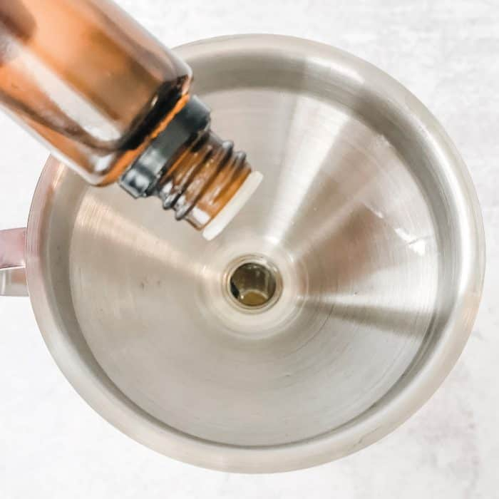adding drops of sweet orange essential oil into bottle through a funnel