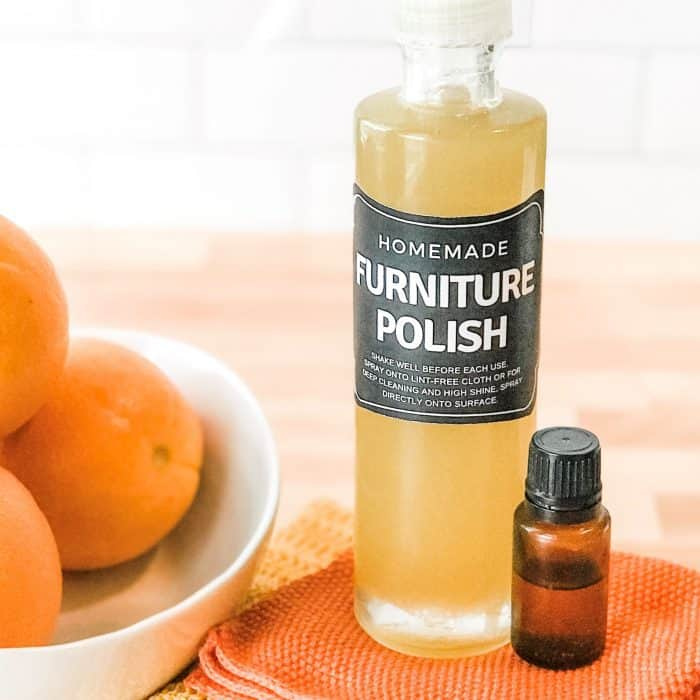 Homemade DIY furniture polish in custom bottle with bottle of sweet orange essential oil and bowl of oranges