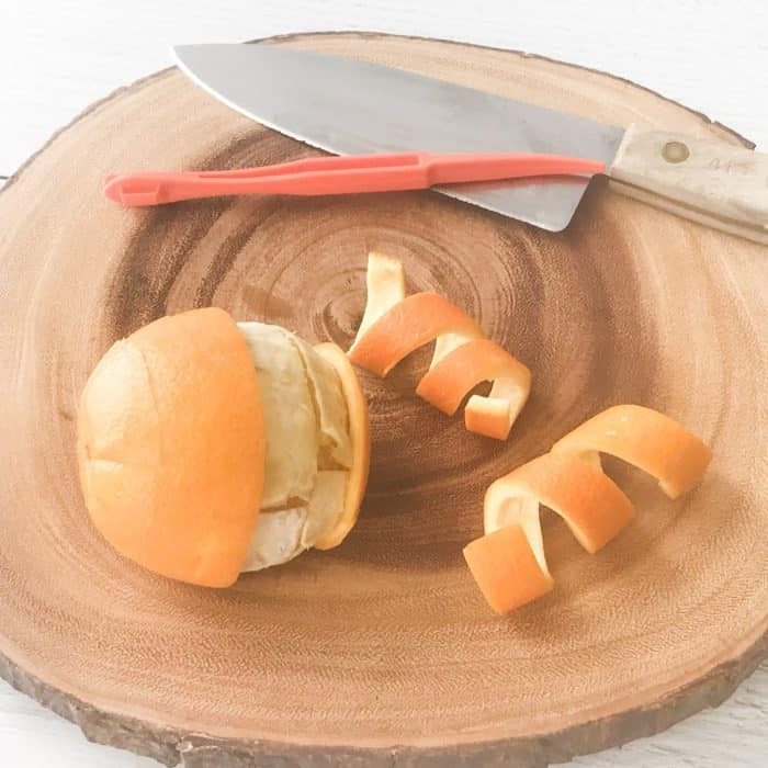 orange with peels, citrus peelers, knife, on cutting board
