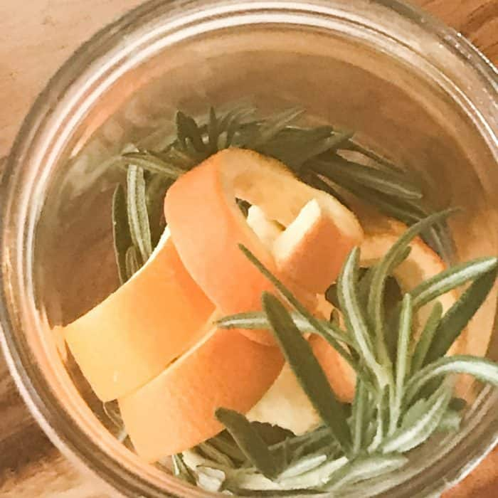 overhead shot of orange peels and rosemary sprigs in clear glass jar, ingredient for floating scented candles with essential oils
