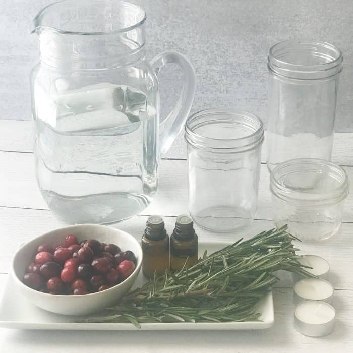 rosemary sprigs, cranberries, essential oil bottles, pitcher of water, clear glass jars, essential oil bottles, ingredients for scented floated candles with essential oils