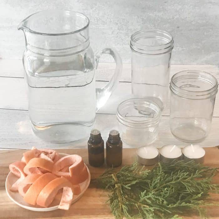 orange peels, rosemary sprigs, cranberries, essential oil bottles, pitcher of water, clear glass jars, essential oil bottles, ingredients for scented floated candles with essential oils