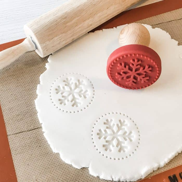 snowflake cookie stamps into salt dough scented with essential oils, on silpat next to rolling pin