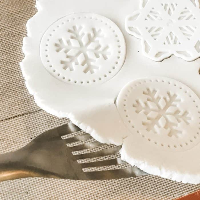 Lifting salt dough with spatula with snowflake cookie cutter and cookie stamp shapes cut out