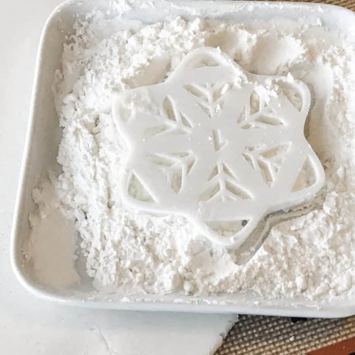 snowflake cookie cutter dipped in bowl of flour