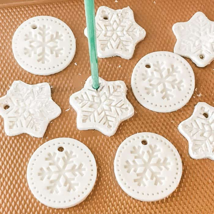 homemade salt dough ornaments scented with essential oils in snowflake shapes, using straw to cut a hole through each one for hanging