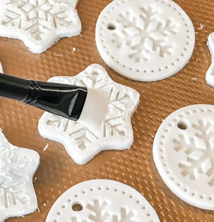 homemade salt dough ornaments in snowflake shapes on cookie sheet, using brush to clean them