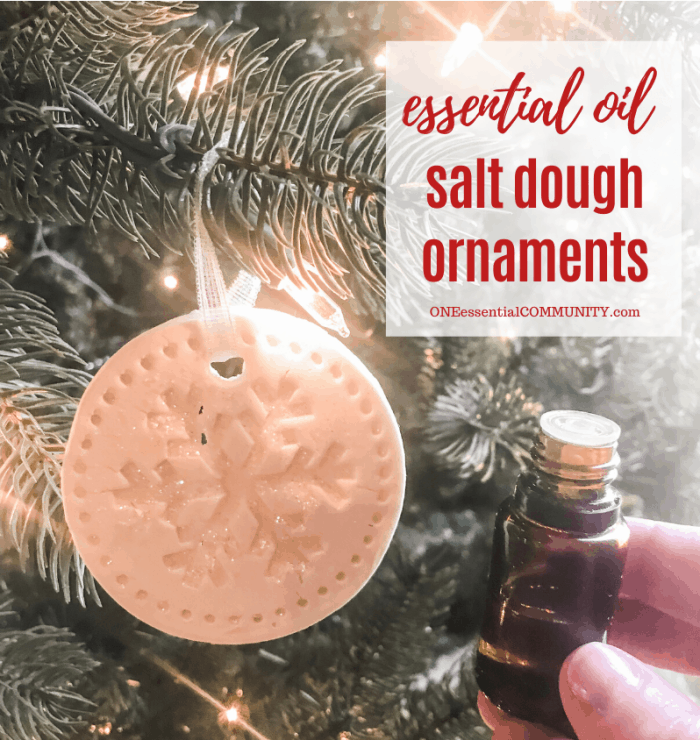 essential oil salt dough ornaments title image, snowflake-shaped ornament hanging from Christmas tree, hand-held essential oil bottle next to tree