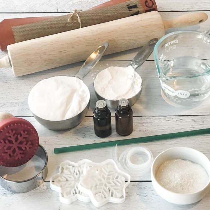 Layout of salt dough ingredients and tools, baking soda, cornstarch, essential oils, silpat, rolling pin, measuring cup and spoons, snowflake cookie cutters