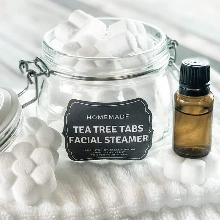 homemade tea tree tabs facial steamer with essential oil in open glass jar with custom label next to essential oil bottle
