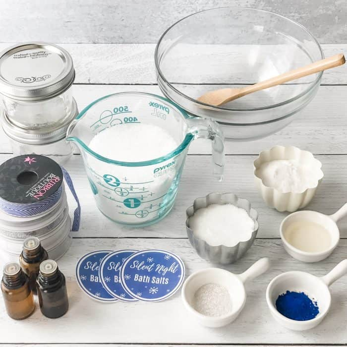 Silent Night Bath Salts ingredients display of Epsom salt, sea salt, blue coloring, mica, essential oil bottles, measuring cups and spoons, jars and labels