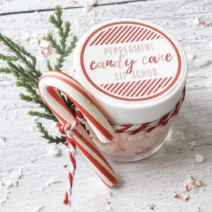 peppermint candy cane lip scrub with essential oils in glass jar with custom label, candy cane and twig garnish tied to jar