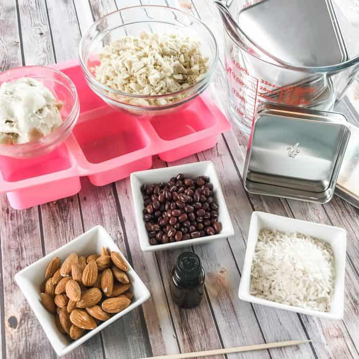 DIY Lush Buffy Bars ingredients and tools - lemon and lavender essential oils, cocoa butter and shea butter, almonds, rice, adzuki beans, silicone molds, Lush tins, measuring cups and bowls