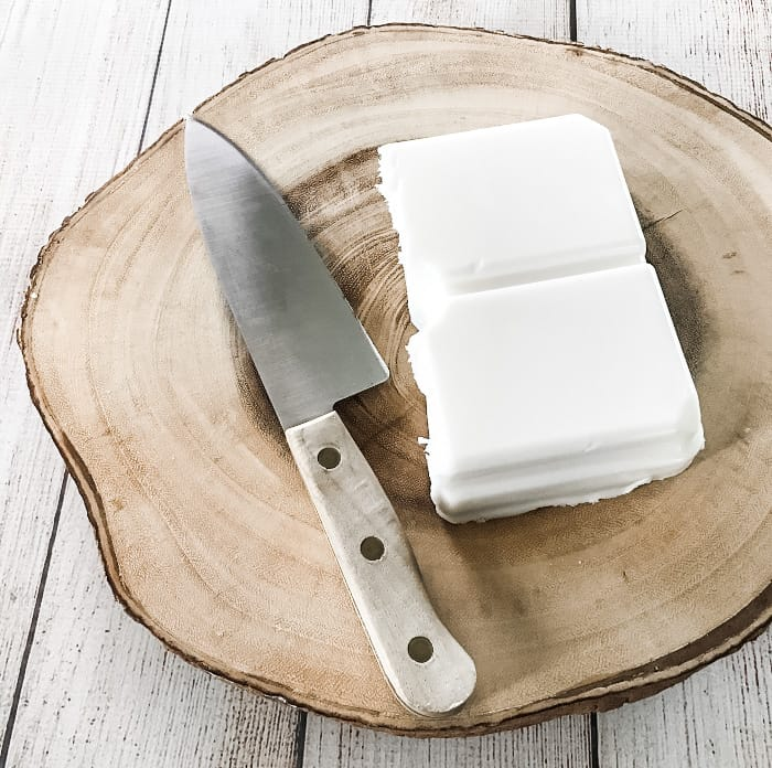 block of goat's milk melt & pour soap on wooden block, next to chef's knife with wooden handle