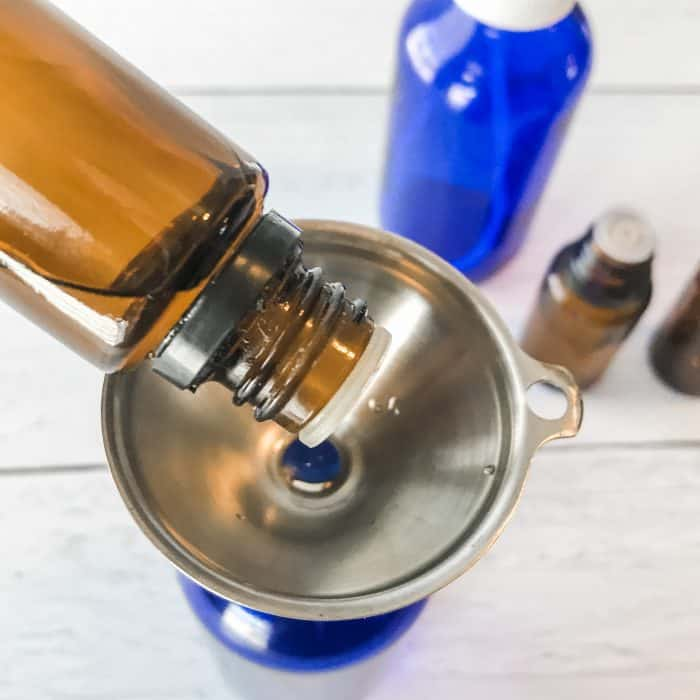 adding essential oil through funnel to spray bottle while making Winter Blues body spray with essential oils