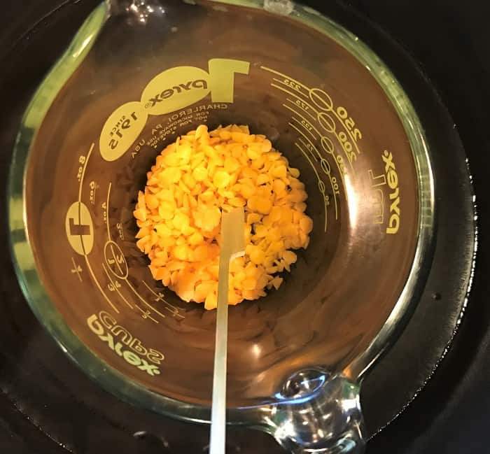 melting beeswax in glass jar for making energy boosting cream with essential oils
