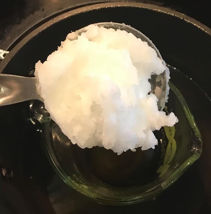 adding coconut oil to melted beeswax for making energy boosting cream with essential oils
