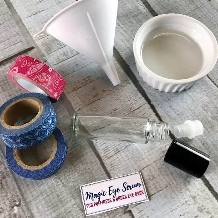 display of ingredients and equipment for making eye serum for puffiness and under eye bags: packing tape, funnel, ramekin, rollerball bottle and cap, custom label
