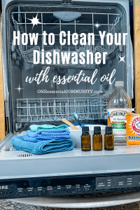 open dishwasher with cleaning supplies (essential oil, vinegar, baking soda)