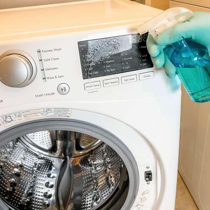 spraying homemade natural cleaner on washing machine