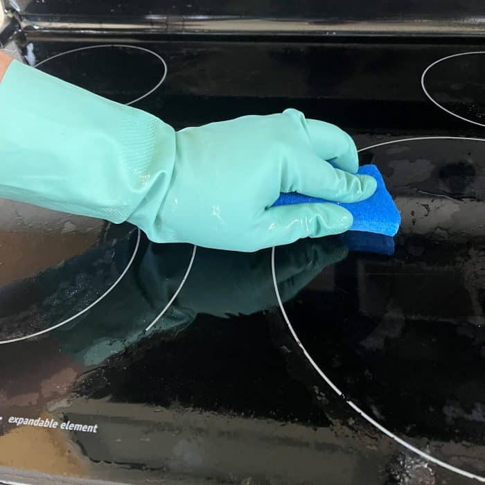 cleaning glass stovetop with sponge