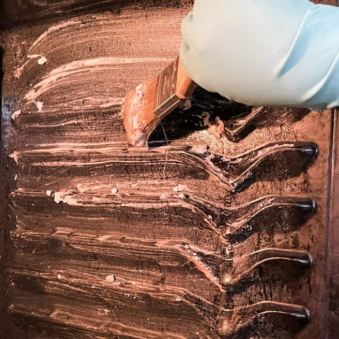 brushing cleaning paste onto oven walls