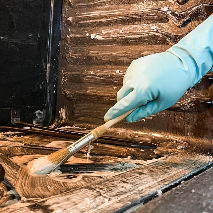 using paintbrush to apply cleaning mixture to bottom of oven