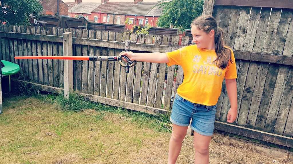 a young girl in tshirt and shorts holding a lightsabre in a grassy garden