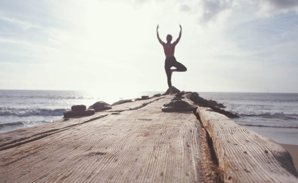 getting healthier - person at the end of a pier in a yoga stance